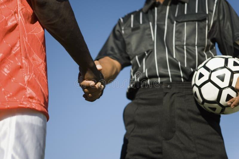 Joueur de football serrant la main avec l'arbitre photographie stock