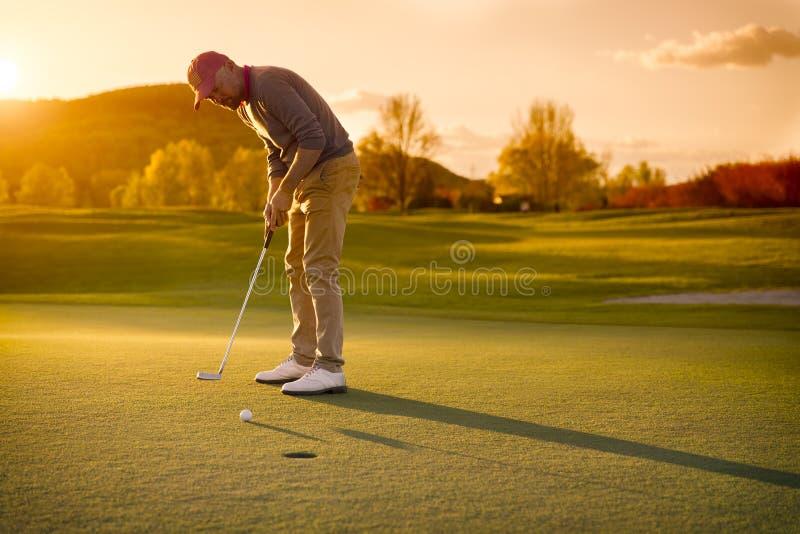 Joueur de golf masculin mettant au coucher du soleil photographie stock libre de droits