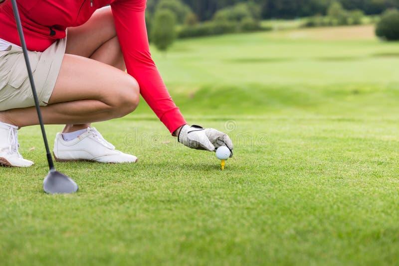 Joueur de golf plaçant la boule sur la pièce en t photo libre de droits