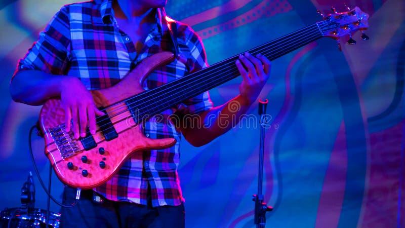 Joueur de guitare basse sur l'?tape du concert ethnique d'air ouvert photos stock