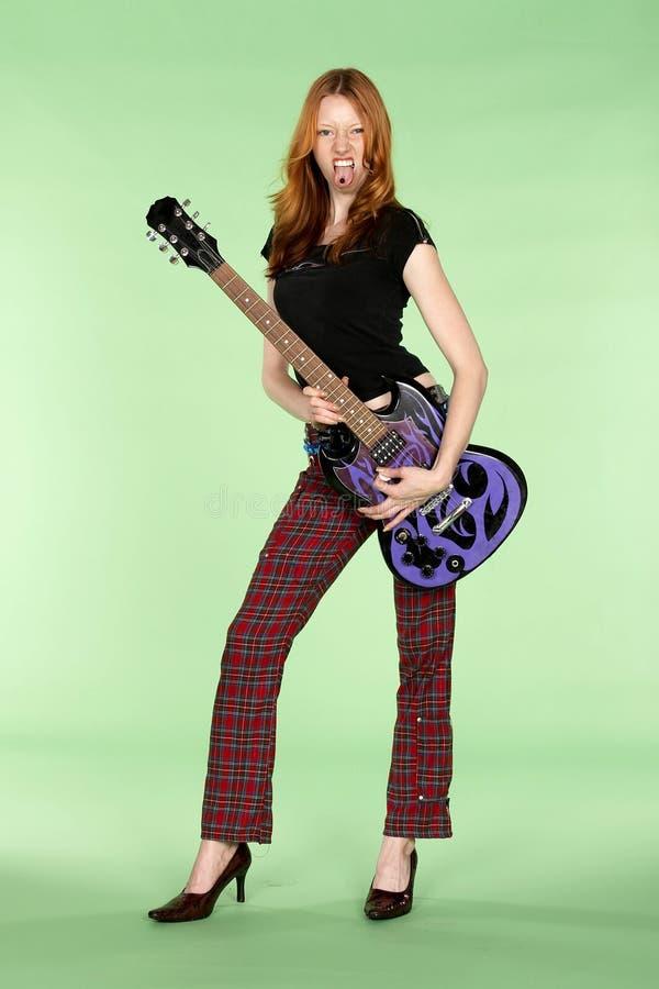 Joueur de guitare principal rouge de rock avec le goujon de Tounge photo stock