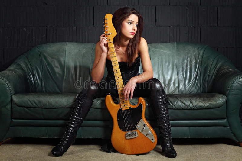 Joueur de guitare sexy s'asseyant sur le divan image stock