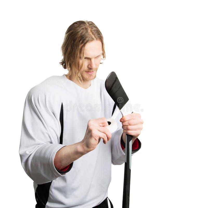 Joueur de hockey attachant du ruban adhésif au bâton photos libres de droits