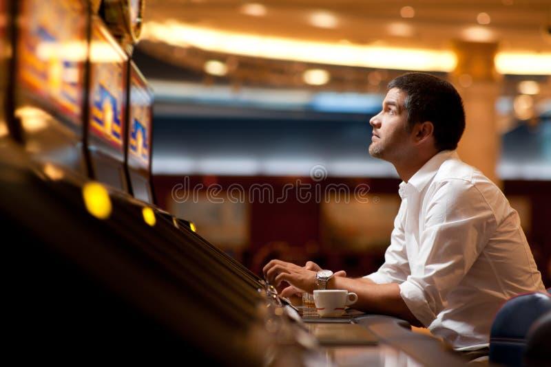 Joueur de machine à sous de casino photos libres de droits