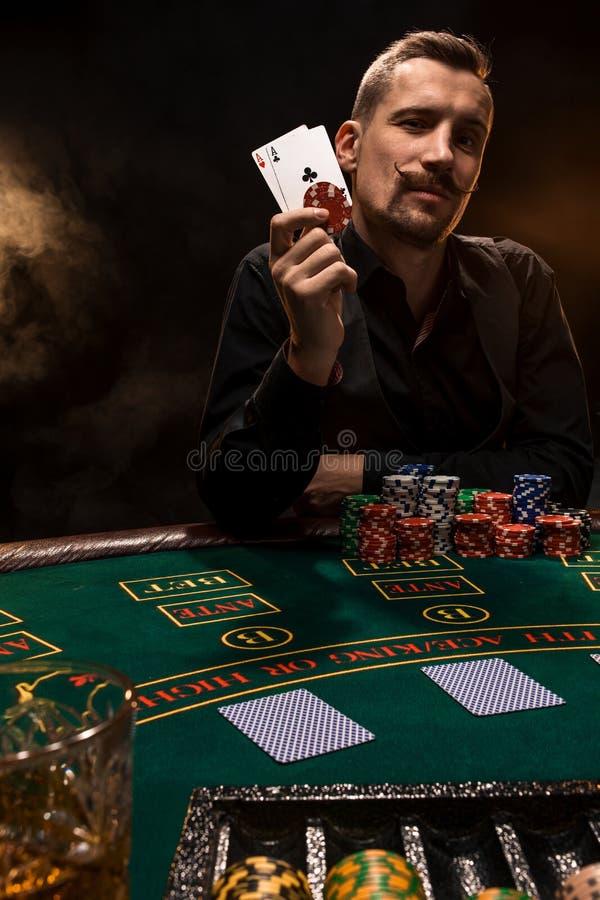 Joueur de poker beau avec deux as dans ses mains et puces se reposant à la table de tisonnier dans une chambre noire complètement photos stock