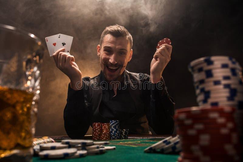 Joueur de poker beau avec deux as dans ses mains et puces se reposant à la table de tisonnier dans une chambre noire complètement images libres de droits