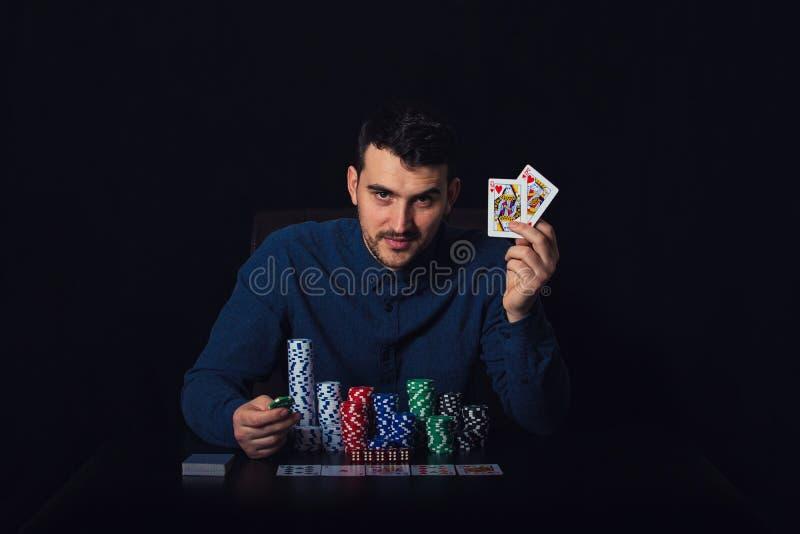 Joueur de poker sûr assis à la table de casino montrant ses cartes de gain au-dessus de fond noir Gagnant de jeu de tournoi images stock