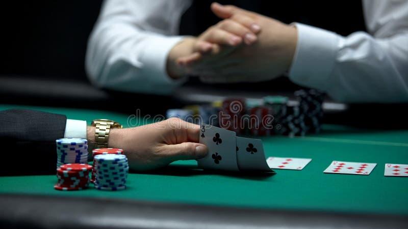 Joueur de poker vérifiant la mauvaise combinaison des cartes occupées par le croupier, main faible image libre de droits