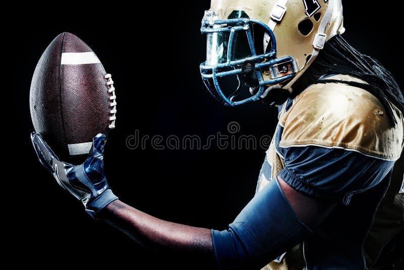 Joueur de sportif de football américain d'isolement sur le fond noir photographie stock