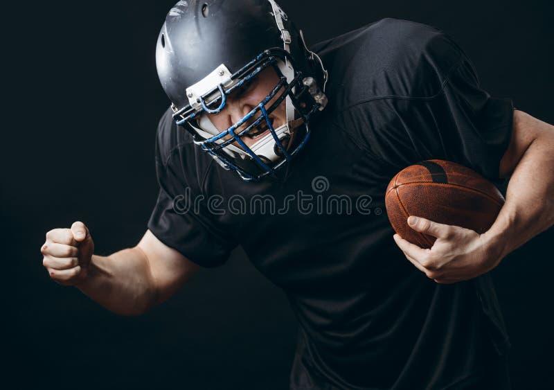 Joueur de sportif de football américain dans l'action d'isolement au-dessus du mur noir de studio photos libres de droits