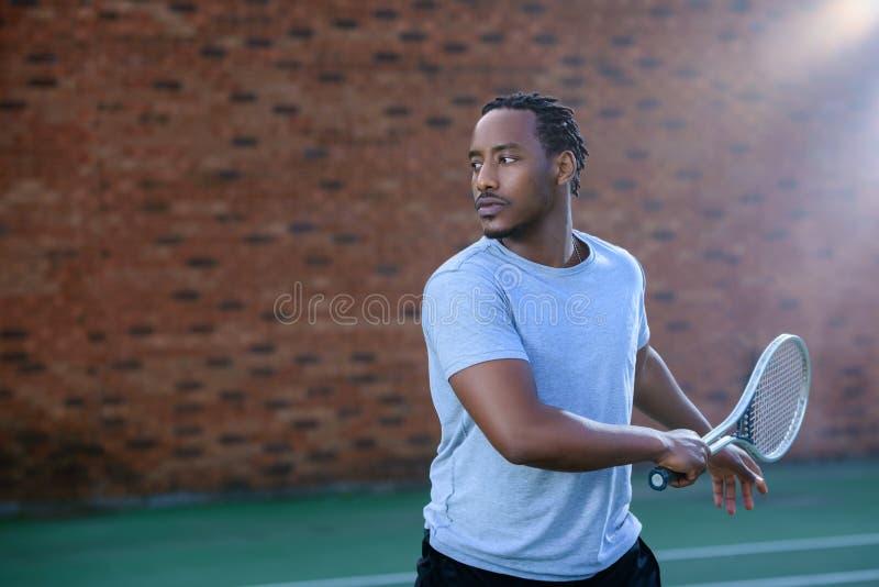 Joueur de tennis donnant une oscillation en revers sur le court de tennis photo stock