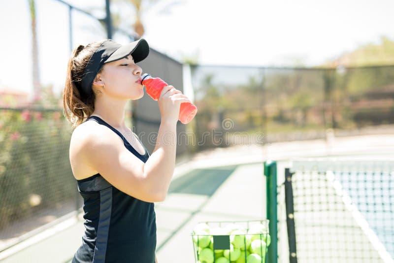 Joueur de tennis féminin ayant la boisson d'énergie images stock