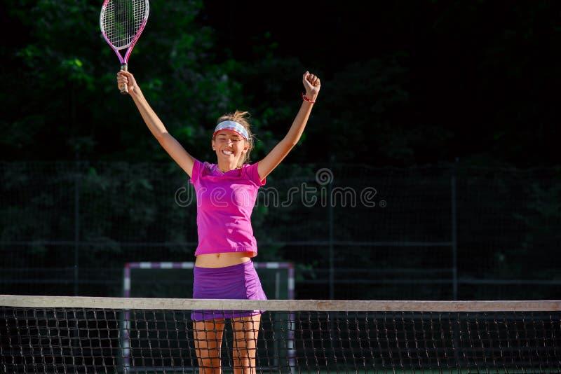 Joueur de tennis féminin heureux sautant près du net et riant, la célébrant gagnant dans le match de tennis Sport, sant? images libres de droits