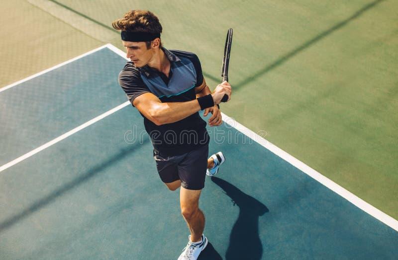 Joueur de tennis frappant des avant-main puissantes dans un jeu photo stock