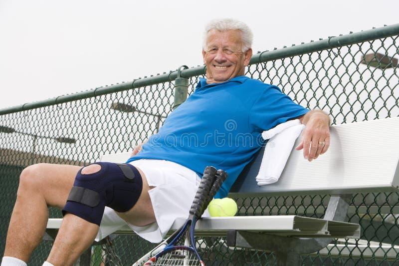 Joueur de tennis supérieur détendant sur le banc images libres de droits