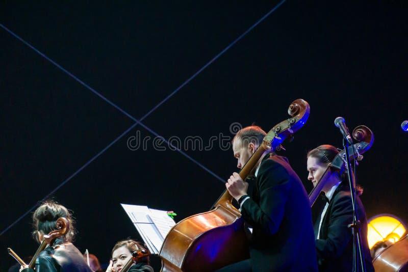Joueur de violoncelle dans l'orchestre symphonique avec des interprètes sur le fond photo stock