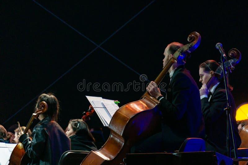 Joueur de violoncelle dans l'orchestre symphonique avec des interprètes sur le fond images libres de droits