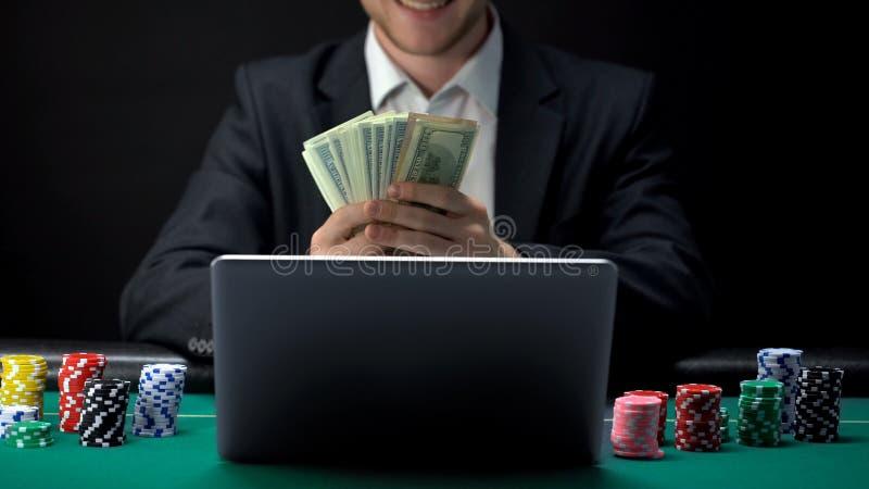 Joueur en ligne réussi de casino comptant l'argent devant l'ordinateur portable, gagnant parié photos stock