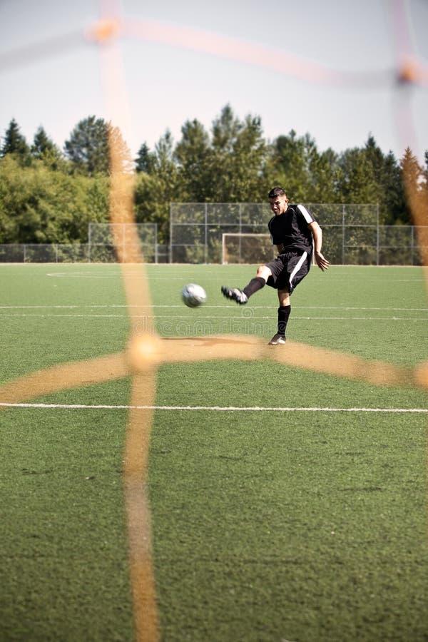 Joueur hispanique de football ou de football donnant un coup de pied une bille image libre de droits