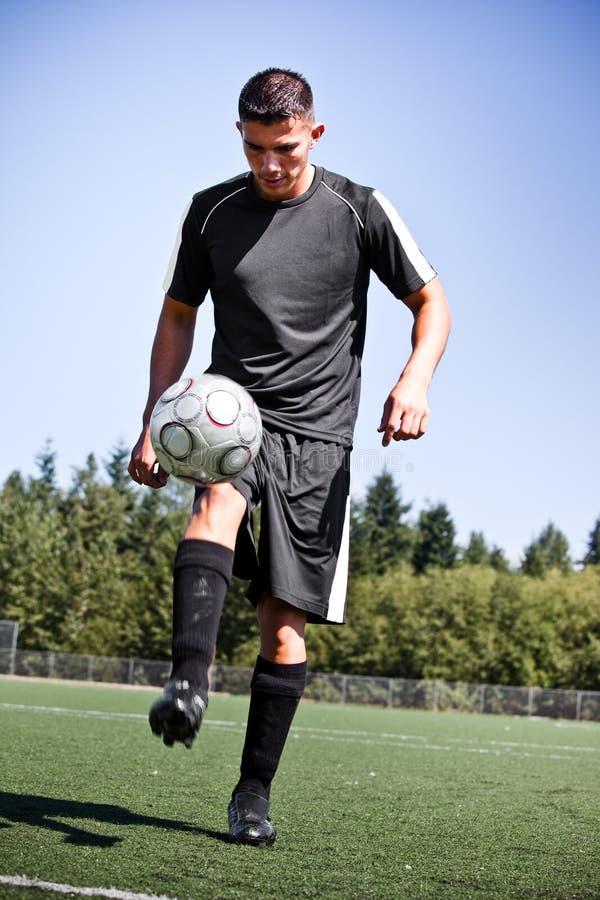 Joueur hispanique de football ou de football donnant un coup de pied une bille photo stock