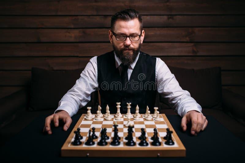 Joueur masculin contre l'échiquier avec des morceaux réglés image stock