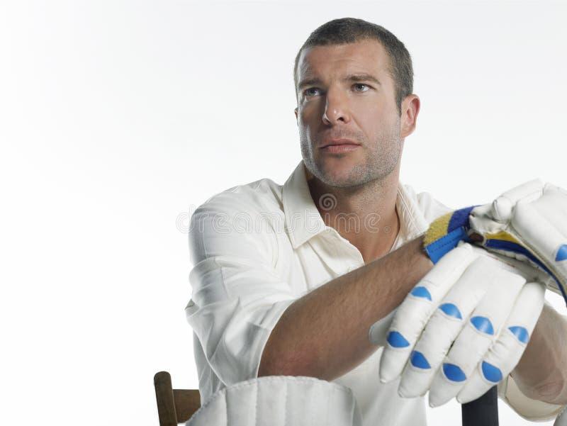 Joueur sérieux de cricket s'asseyant dans la chaise photo stock