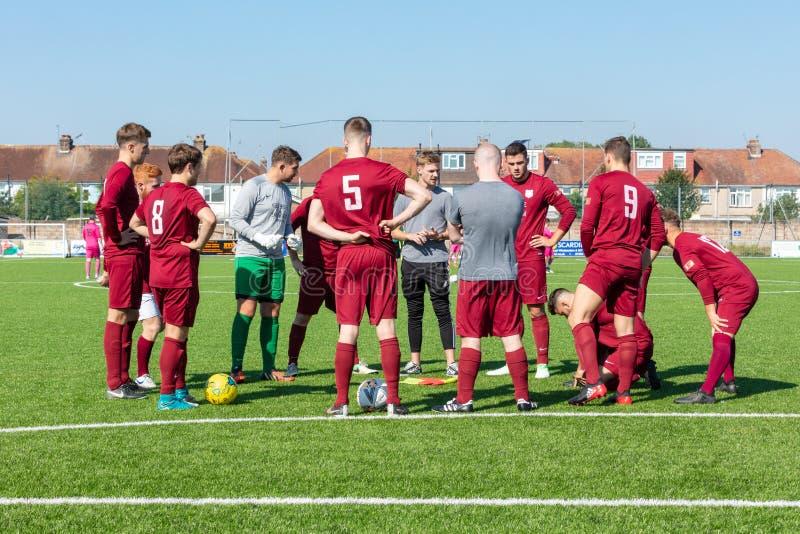 Joueurs écoutant Teamtalk sur le terrain de football photo stock