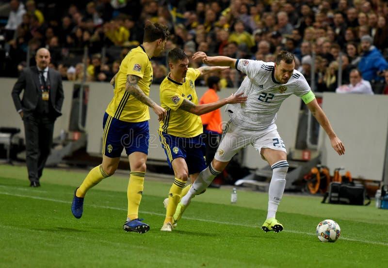 Joueurs d'équipe nationale de la Suède Mikael Lustig et Victor Lindelof contre le gréviste Artem Dzyuba d'équipe nationale de la  photo stock
