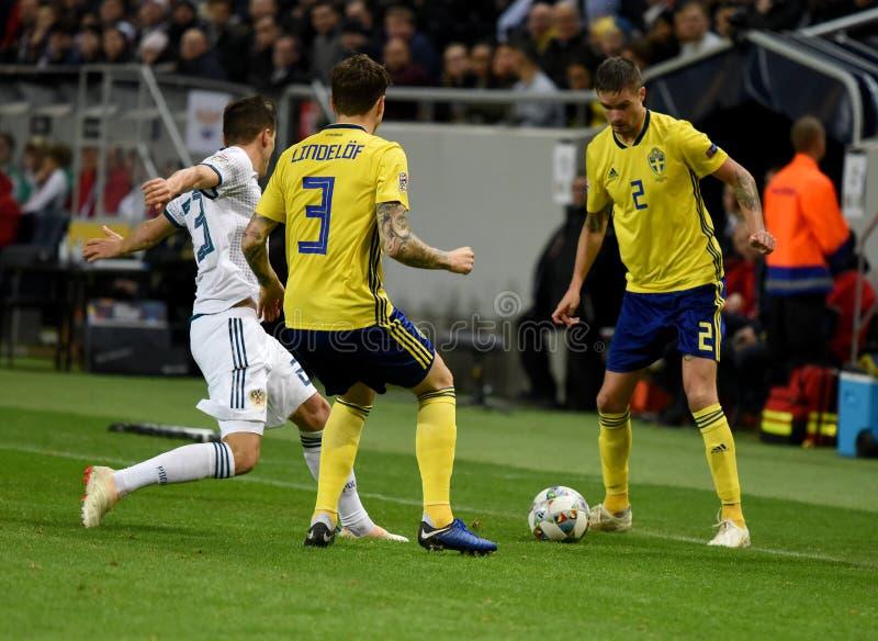 Joueurs d'équipe nationale de la Suède Mikael Lustig et Victor Lindelof contre le gréviste Dmitry Poloz d'équipe nationale de la  image libre de droits