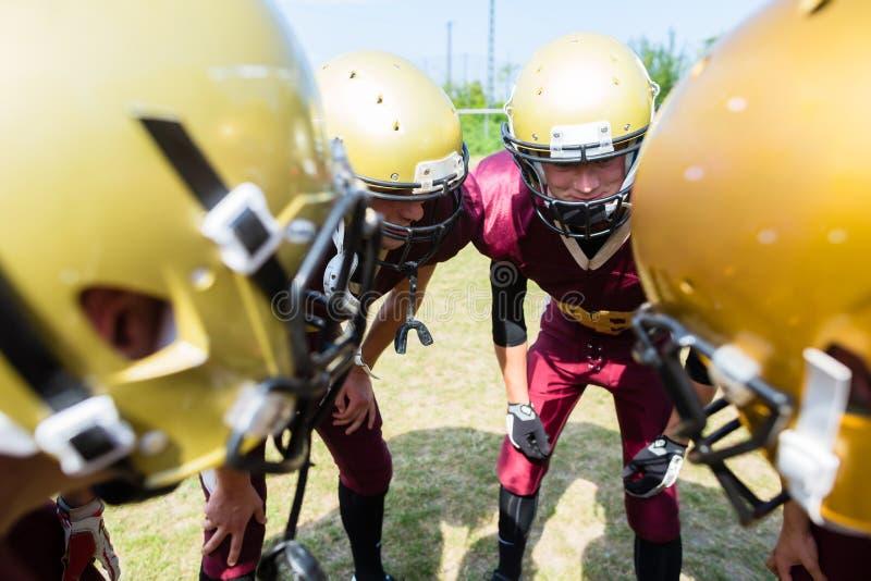 Joueurs de football américain au petit groupe de stratégie images libres de droits
