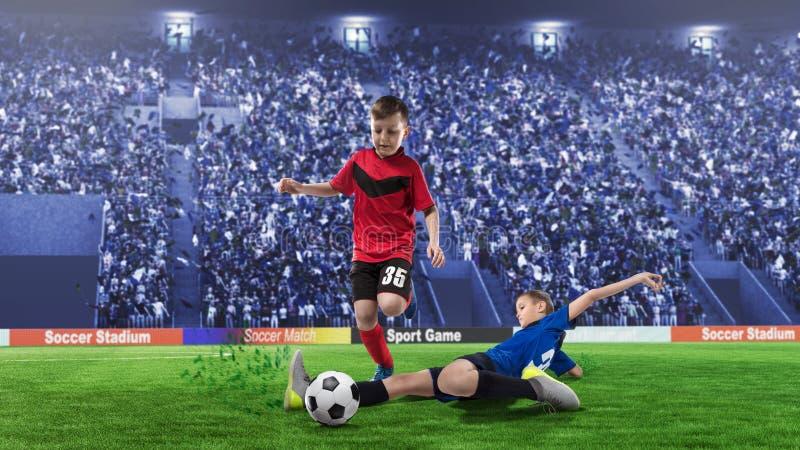 2 joueurs de football d'enfants dans la mêlée pour la boule sur un stade photographie stock libre de droits