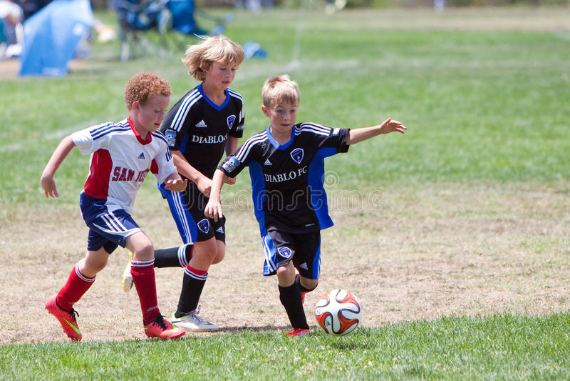 Joueurs de football du football de la jeunesse courant avec la boule images libres de droits