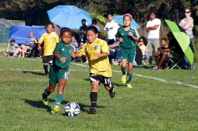 Joueurs de football du football de la jeunesse de filles courant pour la boule image libre de droits