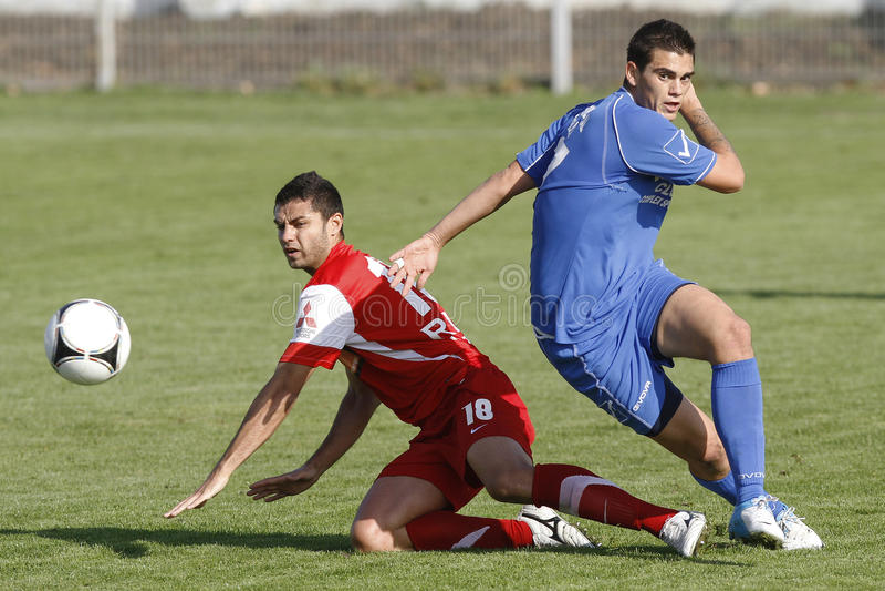 Joueurs de football luttant pour la boule images stock