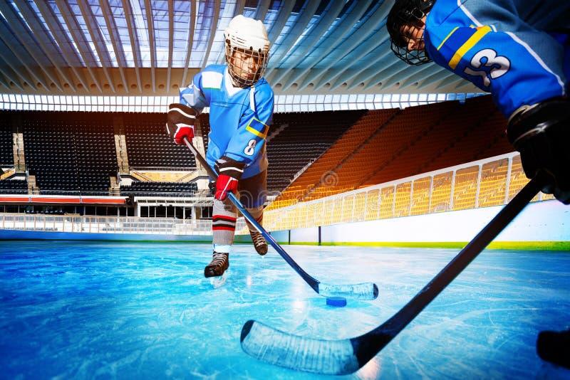 Joueurs de hockey contestant pour le galet sur la patinoire image libre de droits