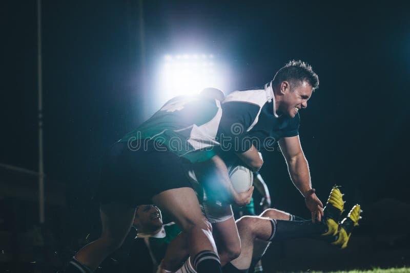 Joueurs de rugby bloquant l'adversaire photo libre de droits