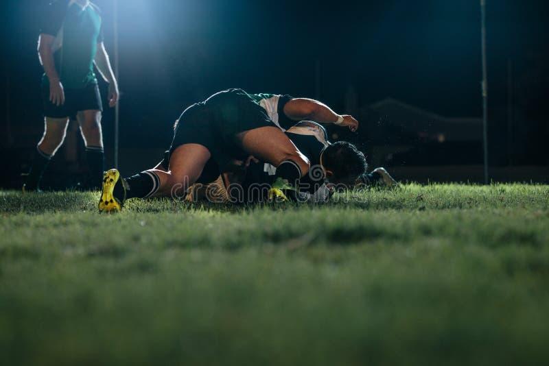 Joueurs de rugby essayant d'obtenir la boule sur l'ar?ne de sports image stock
