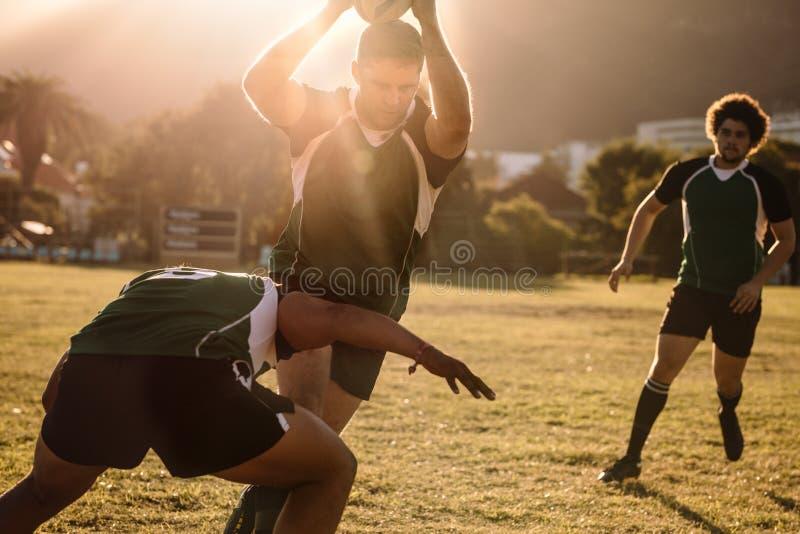 Joueurs de rugby luttant pour la boule photos libres de droits