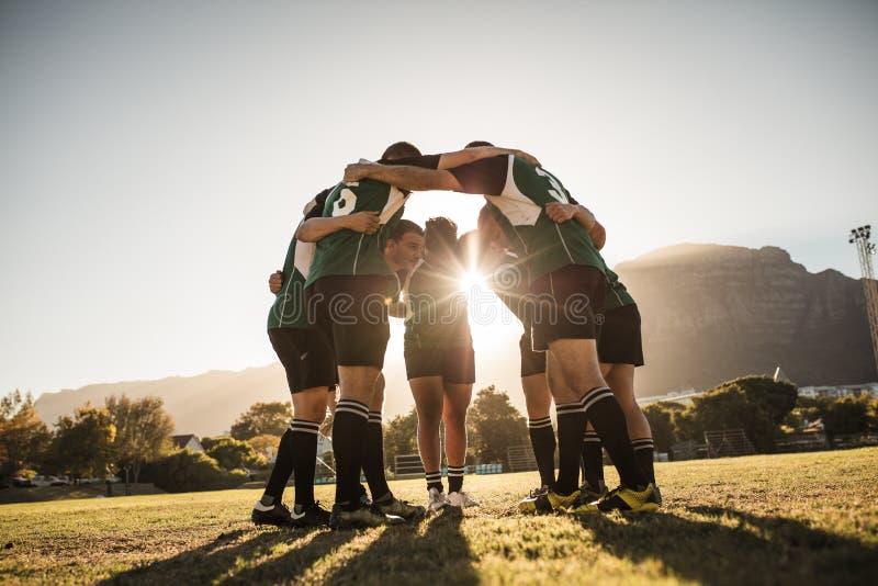 Joueurs de rugby se blottissant sur le champ de sports photos stock
