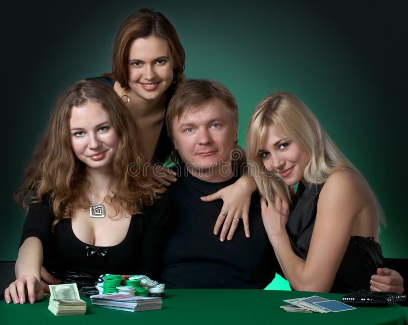 Joueurs de tisonnier dans le casino avec des cartes et des puces image stock