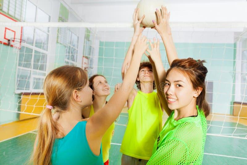 Joueurs de volleyball adolescents avec la boule à côté du filet image stock