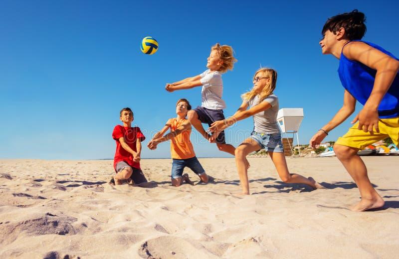 Joueurs de volleyball faisant une bosse passer dessus la plage photographie stock libre de droits