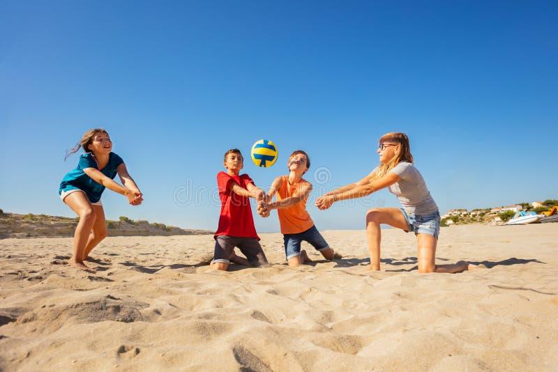 Joueurs de volleyball heureux de plage faisant le passage d'avant-bras images stock