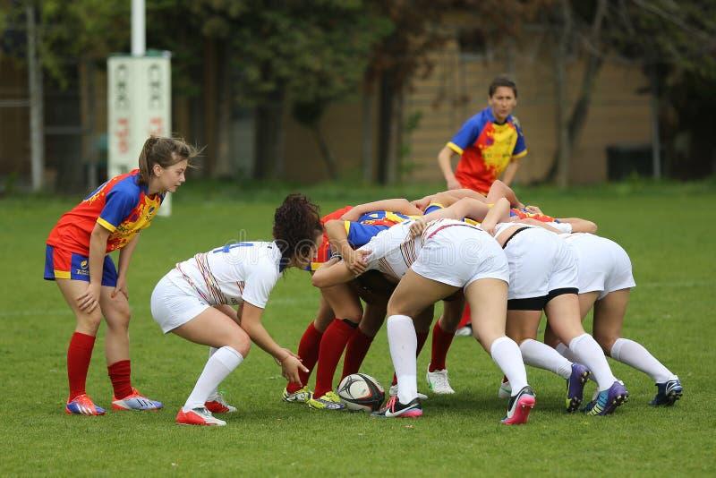 Joueurs féminins impliqués dans une bousculade de rugby photo stock