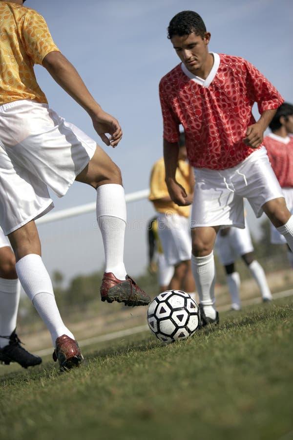 Joueurs jouant au football photographie stock