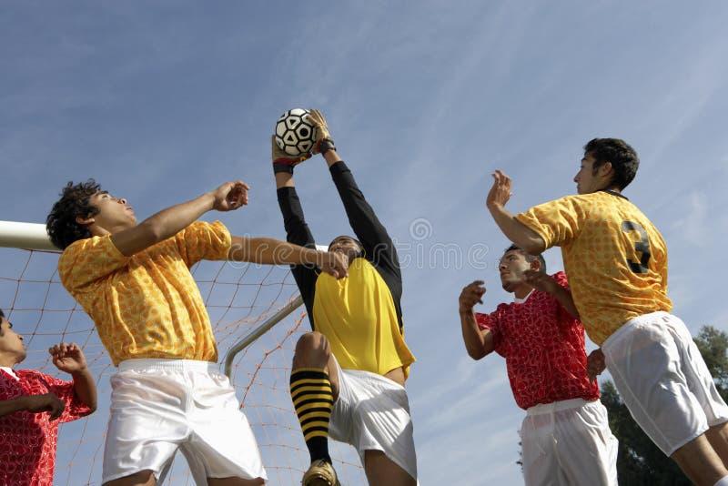 Joueurs jouant le football contre le ciel photos stock