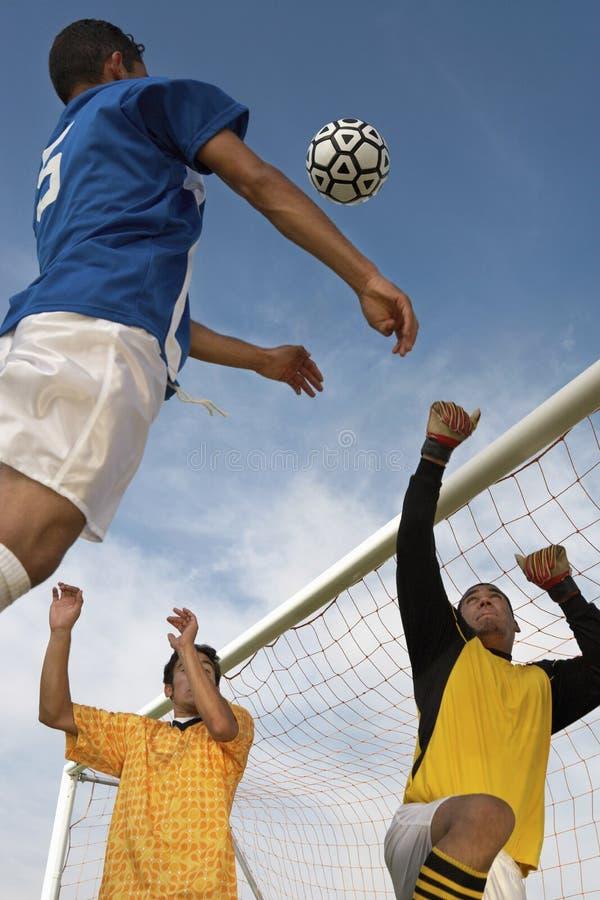 Joueurs jouant le football contre le ciel nuageux image libre de droits