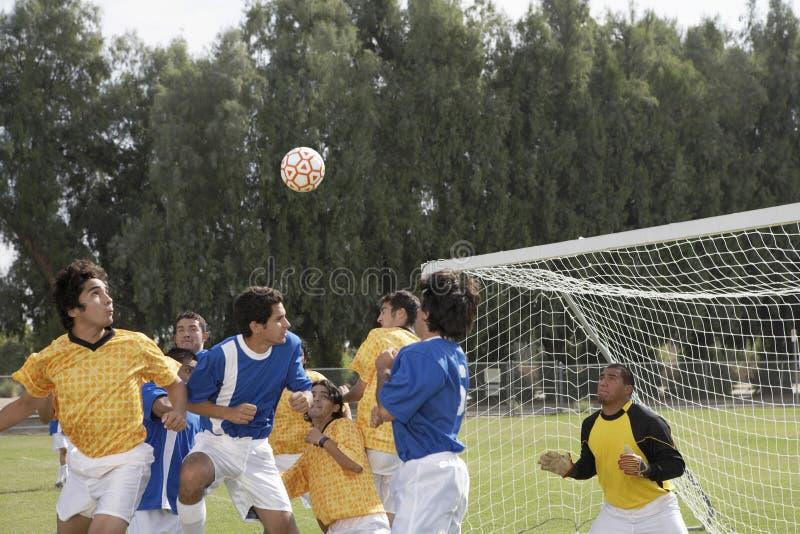 Joueurs jouant le football sur le champ photos stock