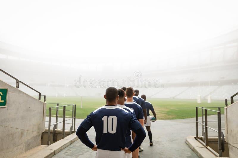 Joueurs masculins divers de rugby se tenant à l'entrée du stade dans une rangée pour le match image libre de droits