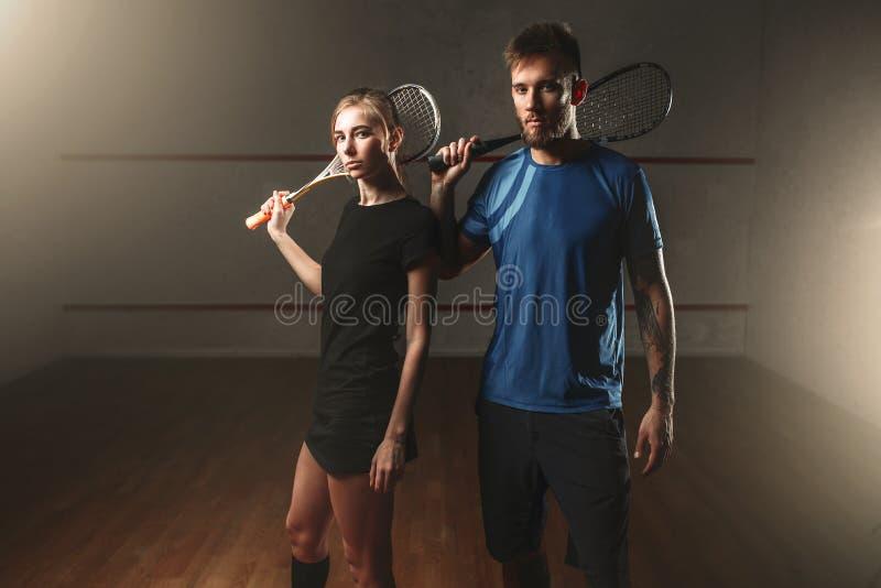 Joueurs masculins et féminins de jeu de courge avec des raquettes photo stock